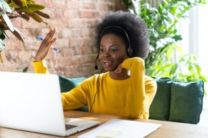 Black girl employee wear headphones talking on video call with clients on laptop consulting customer